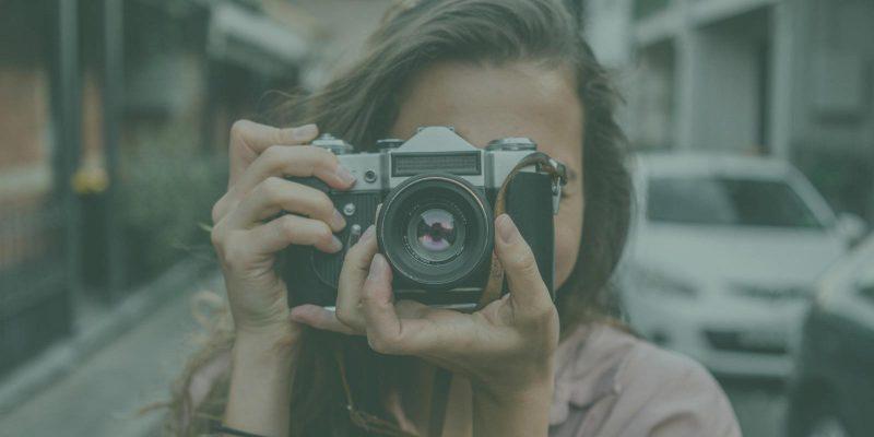 Woman aiming camera at viewer